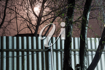 night photography. Moon over the fence and trees