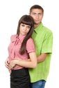 Young couple in a plaid colored clothes hug on white in studio.