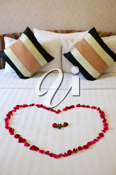 Heart of rose petals laid out on the bed, honeymoon