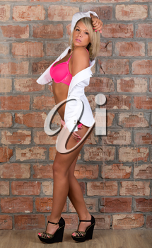 Sexy girl in a white jacket and shorts in interior with brick wall