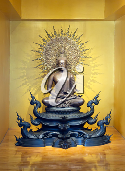 A golden buddha statue sits in peaceful meditation