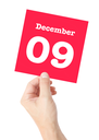 December 9 written on a card held by a hand