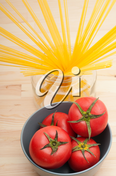 fresh tomato and raw spaghetti pasta over pine wood table