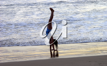 Royalty Free Photo of a Little Girl Doing A Handstand On The Beach