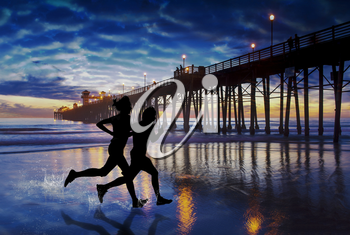 Two friends splash down the coast in the last light near the Oceanside Pier. Oceanside is 40 miles North of San Diego, California.