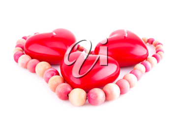 Red heart candles and wooden necklace isolated on white background.