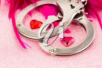 Handcuffs, pink feather and hearts on sparkling background.