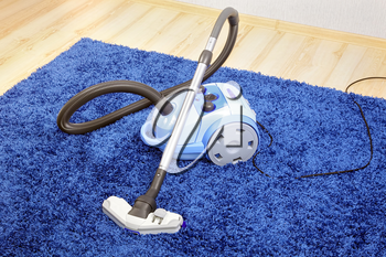 Powerful vacuum cleaner stand  on blue carpet.