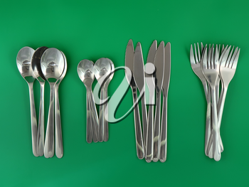 Table serving-knife,plate,fork and   on  green background.