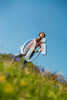 beautiful woman in jeans standing on the grass