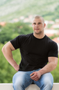 Happy Muscular Man In Black T-Shirt Standing And Showing His Muscle