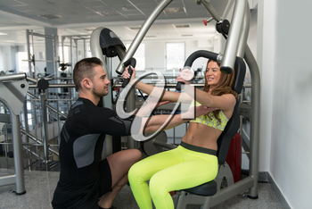Personal Trainer Showing Young Woman How To Train Chest On Machine In The Gym
