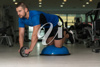 Personal Trainer Doing A Exercise For Abs With Bosu Balance Ball As Part Of Bodybuilding Fitness Training