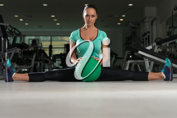 Attractive Woman Doing Stretching With Medicine Ball As Part Of Bodybuilding Training