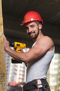Successful Male Architect At A Building Site Trying To Drill A Large Wood Plank