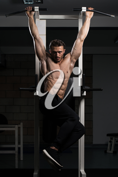Handsome Man Performing Hanging Leg Raises Exercise - One Of The Most Effective Ab Exercises