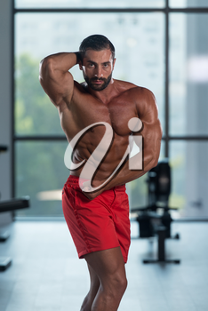 Young Italian Man Standing Strong In The Gym And Flexing Muscles - Muscular Athletic Bodybuilder Fitness Model Posing After Exercises