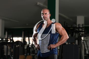 Young Bald Man Standing Strong In The Gym And Flexing Muscles - Muscular Athletic Bodybuilder Fitness Model Posing After Exercises