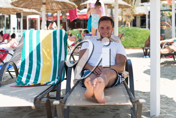 Portrait of Handsome Happy Smiling Man Lying on Chair on Beach by Sea