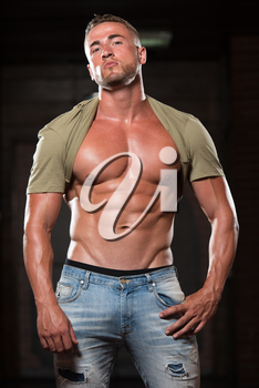 Healthy Young Man In Jeans And T-shirt Standing Strong In The Gym And Flexing Muscles - Muscular Athletic Bodybuilder Fitness Model Posing After Exercises