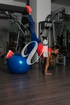 Fitness Woman Working Out Legs On Ball In A Fitness Center - Leg Exercise