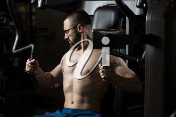 Handsome Muscular Fitness Man Wearing Glasses Doing Heavy Weight Exercise For Chest On Machine With Cable In The Gym