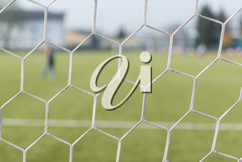 Soccer or Football Net Background - View From Behind the Goal With Blurred Stadium and Field Pitch
