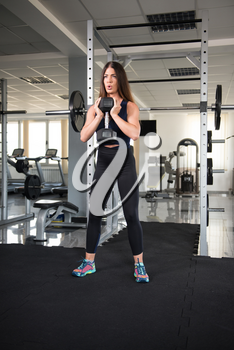 Muscular Fitness Woman Athlete Doing Heavy Weight Exercise For Back and Legs With Dumbbells In The Gym