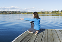 Girl pointing at feeding fish on lake while fishing from wooden dock