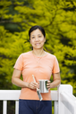 Vertical photo of a mature woman holding paint can and brush while facing forward with white wood deck railing and blurred out green trees behind her