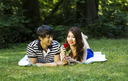 Horizontal photo of young adult couple, lying on blanket, while looking at single red rose with green grass and trees in background