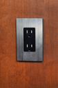 Vertical photo of an electrical outlet and face plate on cherry wood wall