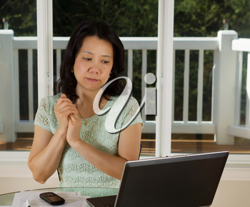 Photo of mature woman looking at computer screen while working at home with laptop, cell phone and papers on top of table and large windows in background