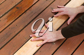 Horizontal photo of male hands putting in a single new cedar wooden board next to fading wood on outdoor deck