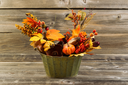 Horizontal photo of home decorations place inside of a metal bucket on rustic wooden boards