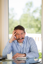 Vertical image of mature man showing extreme stress, looking forward, while working from home with bright daylight coming in from window in background