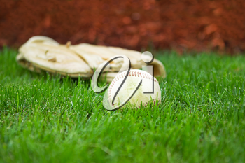 Closeup horizontal photo of old baseball with glove in background on natural grass field