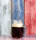 Front view of a single jar glass of cold dark beer.  Faded wooden boards painted red, white and blue in background with USA flag underneath.