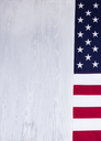 Folded cloth flag, right border, of United States of America on white wood in vertical format.