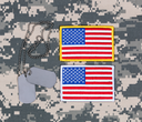 Small USA flag patches and identification tags on military uniform.
