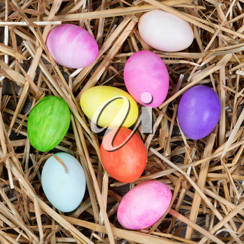 Colorful Easter egg decorations on natural straw and wood. Overhead view.