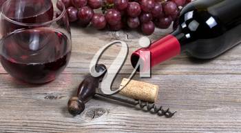 Selective focus on vintage corkscrew with a bottle of red wine, grapes, and drinking glasses in background on rustic wooden boards