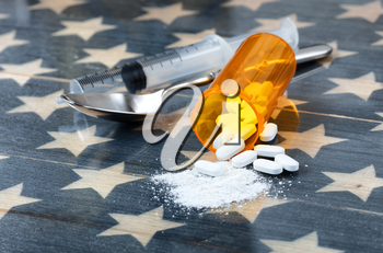 Front view of opioid pain killer tablets with spoon and syringe on rustic USA flag in background for drug addiction concept in America