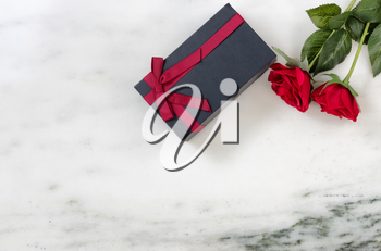 red roses and dark gift box on Marble stone background in flat lay view