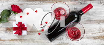 Valentines card, gift, wine and single rose on rustic white wood in flat lay view