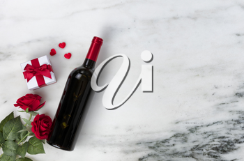 Happy Valentines Day with lovely rose flowers and red wine bottle plus giftbox on natural marble stone