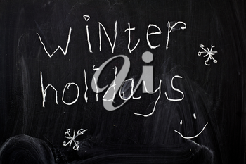 Inscription winter holidays, written by a child's hand on the chalk board