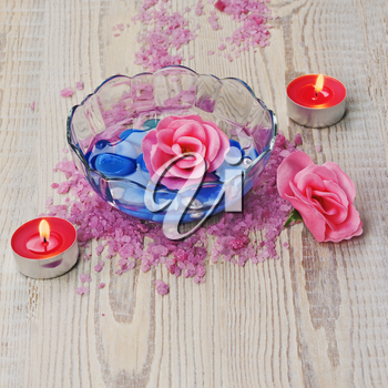 Soap in form of roses in bowl of water on wooden background. Closeup.