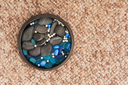 Pearls and colored stones in clay vase on carpet background. Closeup.