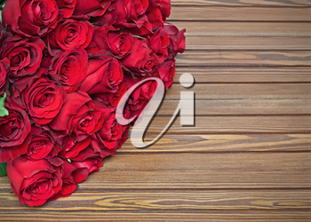 Colorful flower bouquet from red roses on wooden background. Closeup.